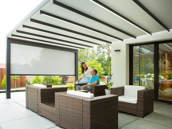 Für zusätzlichen Schutz vor Wind und Wetter oder der Privatsphäre kann das Markisendach um ei-ne Senkrechtmarkise erweitert werden. Foto: © Reflexa