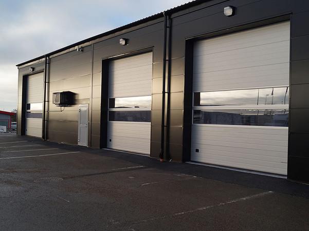 Für eine optimale Kombination aus Isoliervermögen und Lichteinfall bieten sich Sektionstore mit ein oder zwei Fensterabschnitten an. Foto: © Lindab