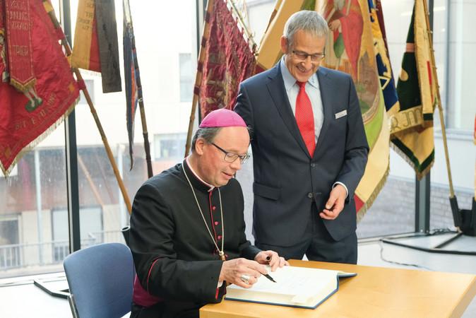 Bischof Dr. Stephan Ackermann trägt sich nach der Segnung ins HWK-Gästebuch ein. Foto: © Foto Braitsch