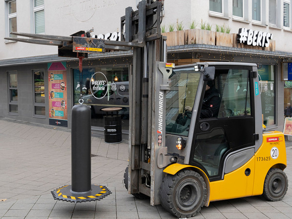Mithilfe einer einschraubbaren Transporthilfe im Pollerdeckel kann die mobile Fahrzeugsperre OktaBlock von Hörmann mit einem Kran oder Stapler einfach platziert werden und ohne technisches Spezialwissen auf- und abgestellt werden. Foto: © Hörmann