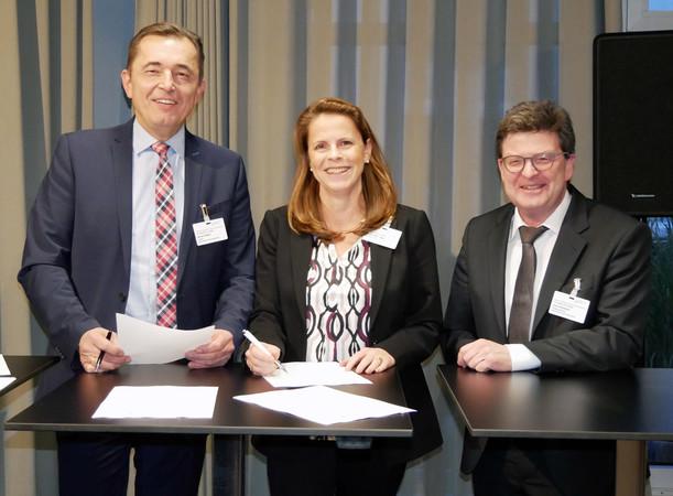 Christin Roth-Jäger, Geschäftsführerin der Roth Werke, unterzeichnet im Beisein von Präsident Hilpert(li.) und Hauptgeschäftsführer Bramann (r.) die HÜV 2.0 des ZVSHK Foto: © ZVSHK
