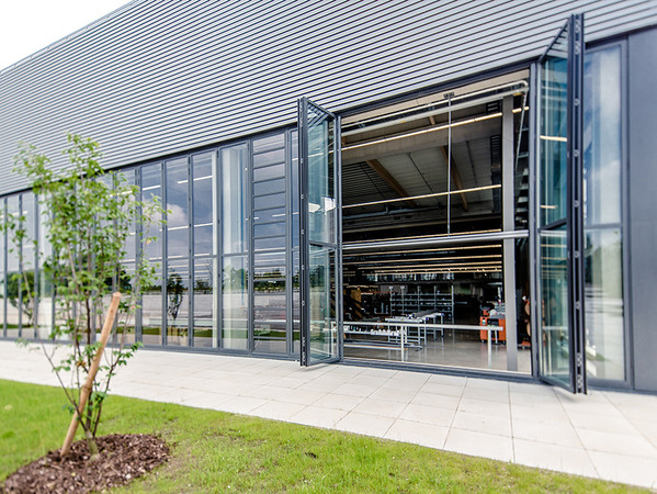 Glas-Faltwände in den Produktionshallen lassen sich komplett zur Seite öffnen und verbinden den Arbeitsbereich mit der anliegenden Natur. Foto: © Solarlux GmbH