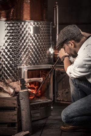 Brennmeister Severin Simon beim Anheizen: Nach dem Brennen ist der Gin klar. Foto: © Severin Simon