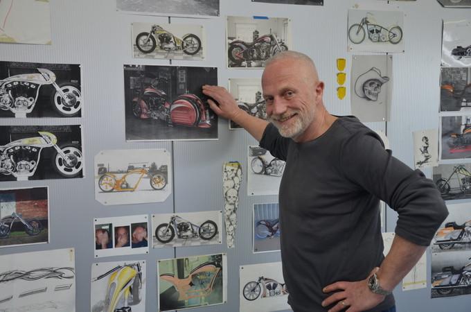 Ingo Kruse vor den Projekt-Zeichnungen und Bildern an der Lackierkabinen-Wand. Foto: © Jürgen Ulbrich