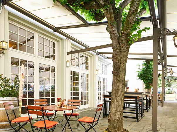 Einige alte Kastanienbäume auf der Terrasse wurden geschickt in das neue Sonnenschutzkonzept integriert. Foto: © Markilux