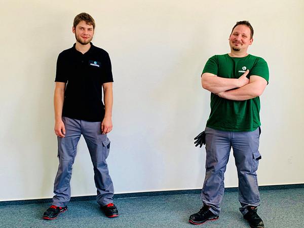 Der Hanno-Nachwuchs strahlt: Adrian Neumann (links) und Joseph Marocsik freuen sich über ihre Ausbildung zum Maschinen- und Anlagenführer. Unterstützt werden sie dabei von erfahrenen Kollegen. Foto: © Hanno Werk GmbH & Co. KG