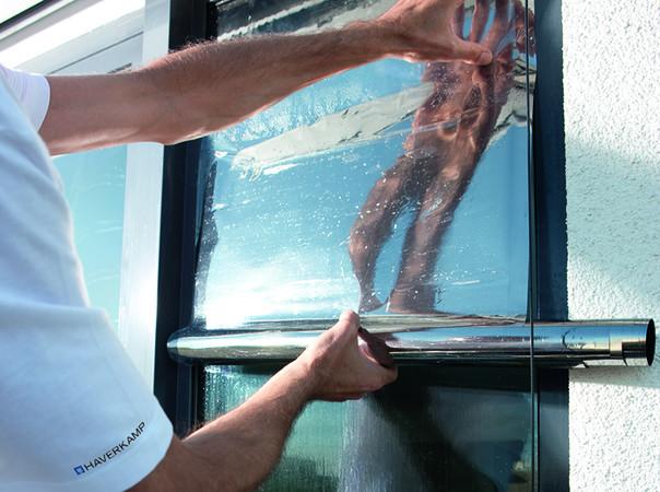 Die Sonnenschutzfolie von Haverkamp wird fachmännisch auf das Glas montiert. Foto: © Haverkamp