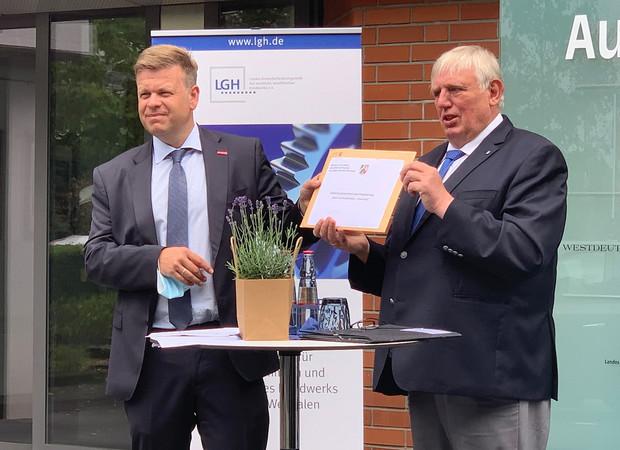 Minister Karl-Josef Laumann (r.) überreicht den Bewilligungsbescheid für das Projekt an Matthias Heidmeier (LGH). Foto: © Kirsten Freund