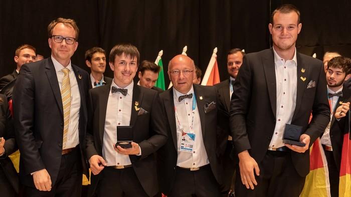 Betonbauer Julian Kiesl (2.v.l.) und Niklas Berroth (r.) freuen sich über ihre Exzellenzmedaille, die sie bei den EuroSkills 2021 in Graz gewonnen haben. Foto: © WorldSkills Germany/Frank Erpinar